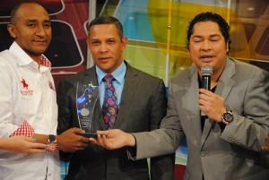 """Franklin Romero recibe un reconocimiento de parte de la producción de """"Domingo y Pachá"""". A la izquierda, el productor Mon Lluberes."""